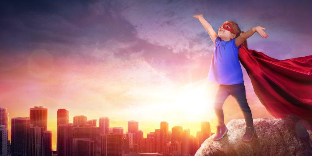 Superhero Child With Cityscape To Sunset